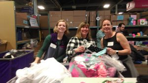 Molly, Susan and Jen take a quick break from sorting clothes to pose for their picture.