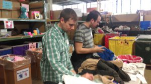 Travis and William hard at work in the Cradles to Crayons warehouse.